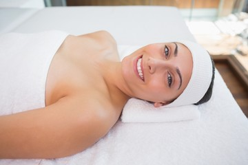 Peaceful smiing brunette lying on massage table