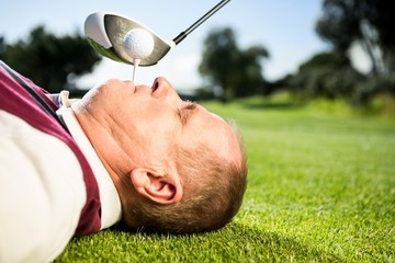 Golfer holding tee in his teeth