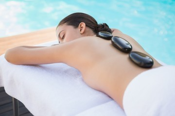 Relaxed brunette lying poolside having a hot stone massage
