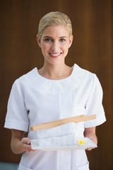 Smiling beauty therapist holding white towels