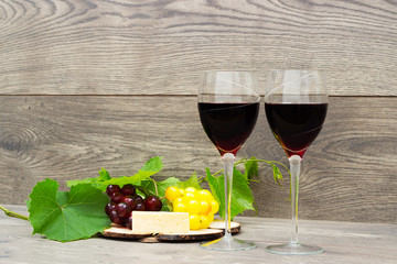 two glasses of wine on a wooden background