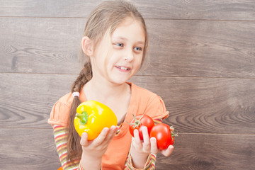 girl holding vegetables on a wooden background