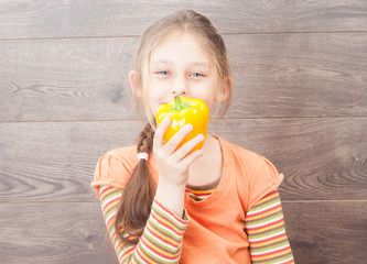little girl holding vegetables on a wooden background