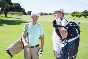 Golfer friends chatting and holding their golf bags