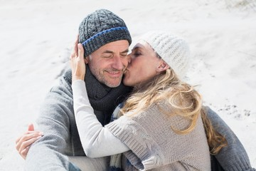 Attractive couple on the beach in warm clothing