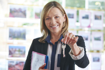 Estate Agent In Office Holding Keys To Property