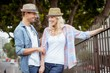 Hip young couple standing by railings