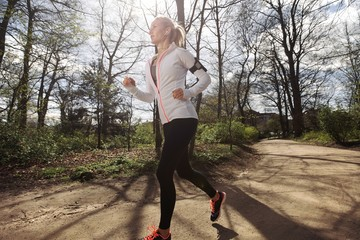 Fit female model jogging in forest