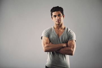 Young muscular man posing against grey background