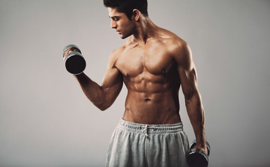Hispanic young man doing heavy dumbbell exercise