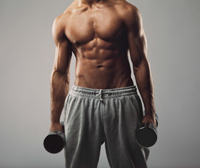 Muscular young man working out with weights
