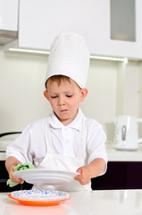 Little boy chef cleaning his plates while cooking