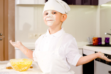 Proud playful little boy in a chefs uniform