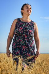 Laughing tanned vivacious woman in a wheat field