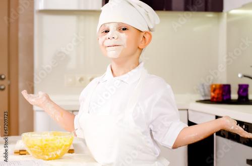Proud playful little boy in a chefs uniform