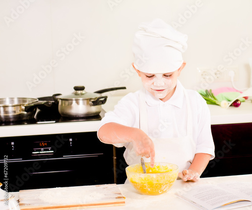 Cute little boy baking in his kitchen at home