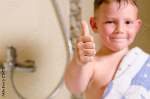 Little boy in the bathroom giving a thumbs up