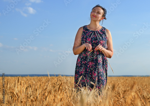 Smiling happy woman in a golden field of wheat