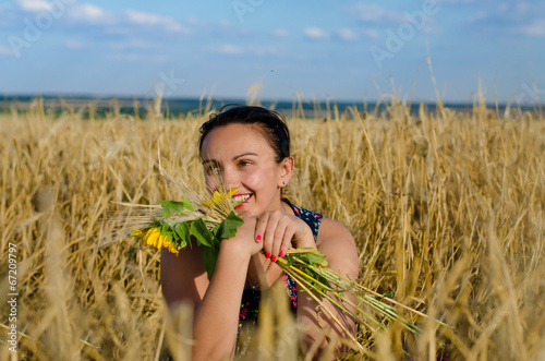 Laughing woman holding flowers in a wheat field