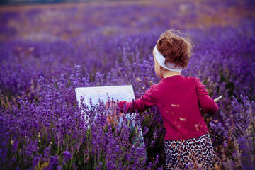 the little girl draws a picture in a lavandovy field