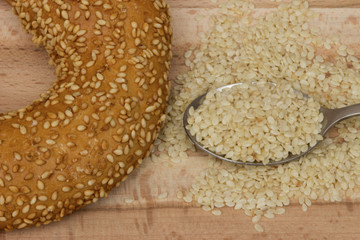 Close-up image of a bagel bread with sesame seeds in spoon