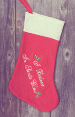 Vintage image of Christmas stocking on wooden background