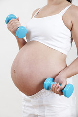 Close Up Of Pregnant Woman Exercising With Weights