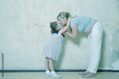 Tochter umarmt Mama mit Babybauch