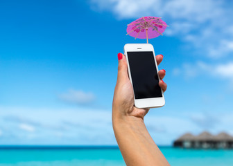 hand showing mobile phone and cocktail umbrella on beach