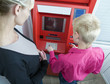 The woman trains the child to receive money from the bank device