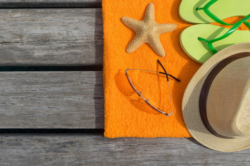 Beach slippers, towel and sunglasses on wood background.
