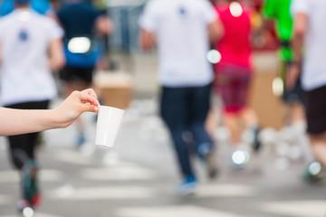 Marathon runner picking up water at service point