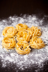 Raw pasta tagliatelle on table