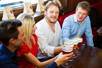 Happy friends clinking with beer mugs in pub