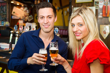 Beautiful couple enjoying beer in a pub