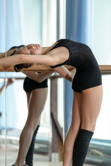 Young ballet dancer stretching out at the barre
