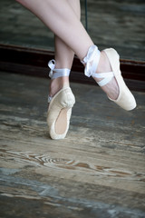 Dancing feet in ballet shoes on wooden floor