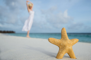 woman dancing on tropical beach against starfish closeup