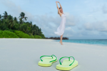 woman  dancing on tropical beach against flip flops closeup