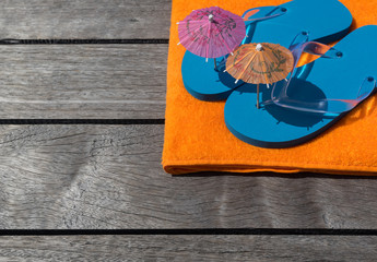 Beach slippers, towel on wood background.