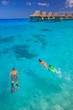 Leinwanddruck Bild - Couple snorkeling in the blue lagoon, Bora Bora, South Pacific