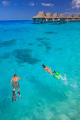 Couple snorkeling in the blue lagoon, Bora Bora, South Pacific