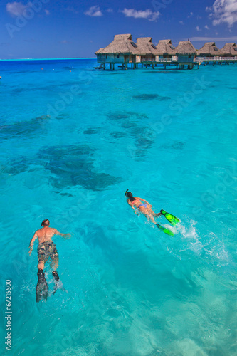Leinwanddruck Bild Couple snorkeling in the blue lagoon, Bora Bora, South Pacific
