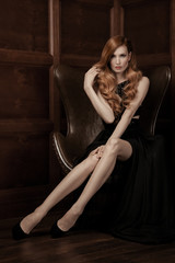 The image of a beautiful luxurious woman sitting on a leather vi