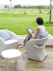 Woman sitting in a chair using tablet pc