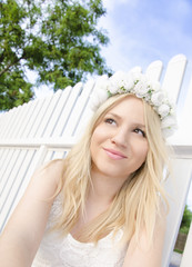 Beautiful young blonde bride white fence backgound