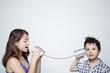 Leinwanddruck Bild - Kids using a can as telephone against gray background