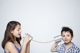 Kids using a can as telephone against gray background
