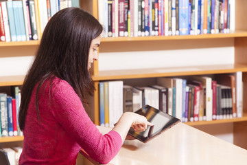 Female student using a tablet computer in a library