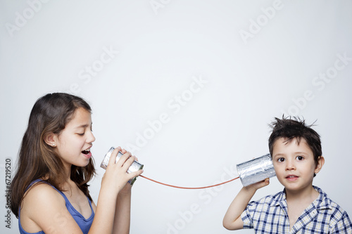 Leinwanddruck Bild Kids using a can as telephone against gray background